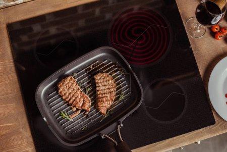 Photo pour Vue de dessus des steaks grillés au romarin dans poêle à induction poêle - image libre de droit