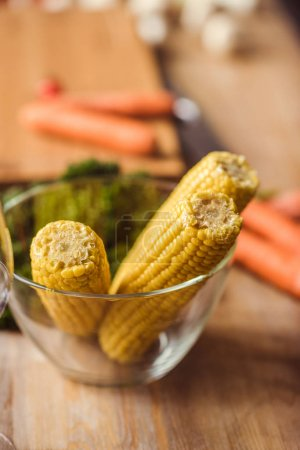 Photo for Close-up view of raw corn cobs in glass bowl on kitchen table - Royalty Free Image
