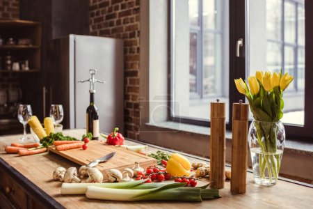 Photo for Fresh vegetables, bottle of wine and flowers in vase on kitchen table - Royalty Free Image