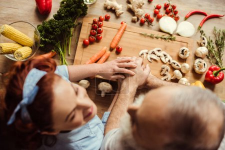 Photo for Overhead view of mature couple preparing vegan food and holding hands - Royalty Free Image