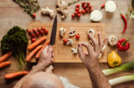 Photo for Overhead view of senior man preparing vegan food and showing ok gesture - Royalty Free Image
