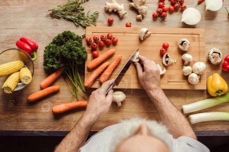 Photo for Overhead view of senior man chopping mushrooms preparing vegan food - Royalty Free Image