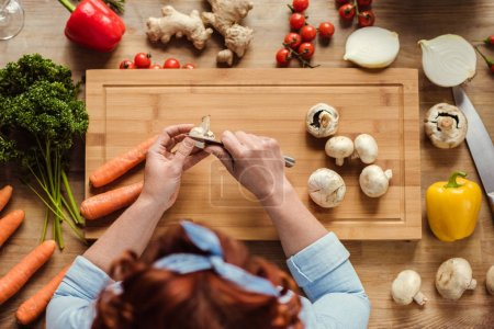 Photo for Overhead view of woman at kitchen table preparing fresh vegetable salad - Royalty Free Image