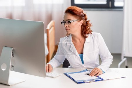 Photo for Concentrated female doctor in eyeglasses using desktop computer in hospital - Royalty Free Image