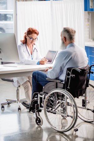 Photo for Mature female doctor showing digital tablet to senior patient in wheelchair - Royalty Free Image