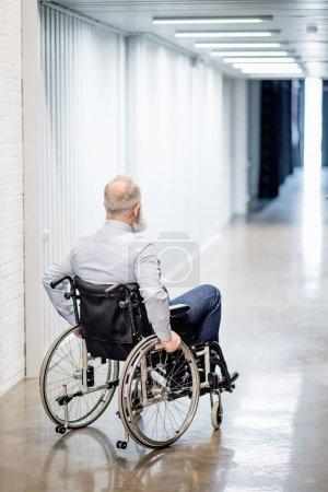 Photo pour Vue arrière du barbu senior en fauteuil roulant dans le couloir de l'hôpital - image libre de droit