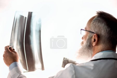 Photo for Senior bearded male doctor in eyeglasses holding x-ray image on white - Royalty Free Image