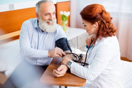 Doctor measuring pressure of patient