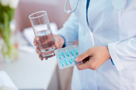 Doctor holding pills and water