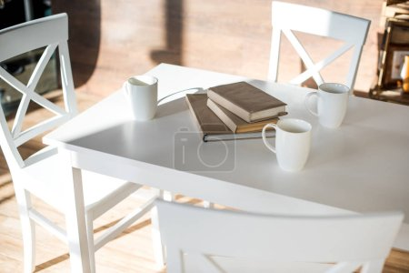 Photo for Books stacked on white table near three coffee cups - Royalty Free Image