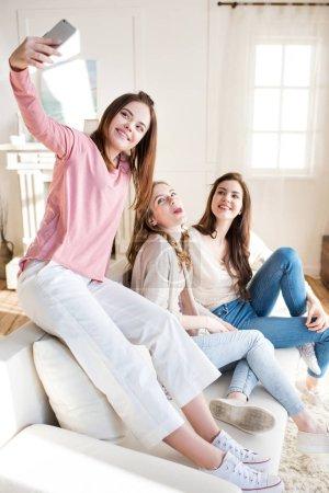Photo pour Trois souriant jeunes femmes assis sur le canapé et prise selfie avec smartphone - image libre de droit