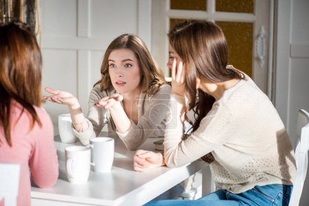 Photo for Attractive young female friends sitting at table with coffee cups and talking - Royalty Free Image