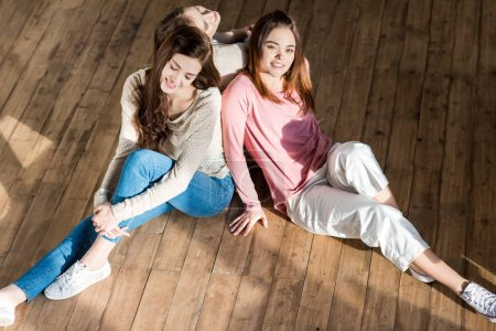 Photo for Three beautiful smiling young women sitting together on wooden floor - Royalty Free Image