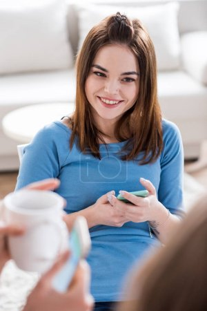 Photo for Portrait of young attractive woman holding smartphone and smiling - Royalty Free Image