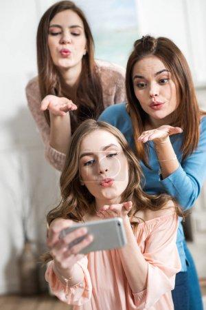 Photo pour Trois jeunes femmes séduisantes souffle baisers tout en faisant selfie - image libre de droit