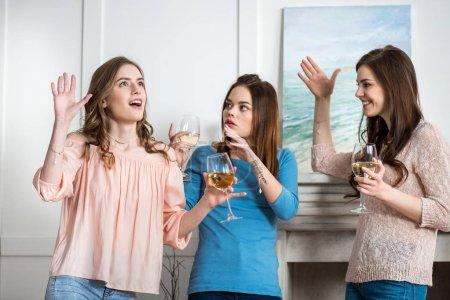 Photo pour Trois heureux jeunes jolies femmes tenant des lunettes avec le vin blanc et gesticulant - image libre de droit