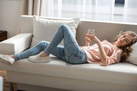 Photo pour Jeune femme souriante attrayante couchée sur le canapé et tenant un verre de vin blanc - image libre de droit