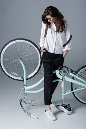 Photo pour Elegant hipster woman with hands in pockets looking at bicycle - image libre de droit