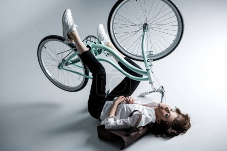 Photo pour Stylish beautiful hipster woman lying with bicycle - image libre de droit