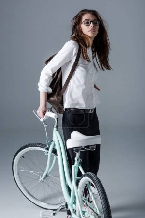 Photo pour Fashionable hipster woman in eyeglasses posing with bicycle - image libre de droit