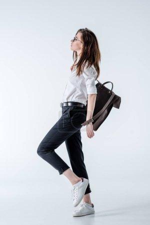 Photo pour Vue latérale de la jeune femme hipster élégante avec sac à dos en cuir posant sur le gris - image libre de droit