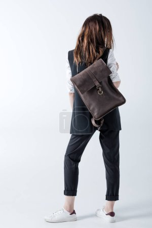 Photo pour Back view of stylish young hipster woman with leather backpack posing on grey - image libre de droit