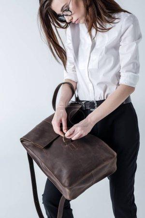 Photo pour Élégant jeune femme hipster dans des lunettes tenant sac à dos en cuir sur gris - image libre de droit