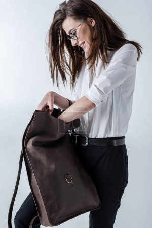 Photo pour Stylish young smiling hipster woman holding leather backpack on grey - image libre de droit
