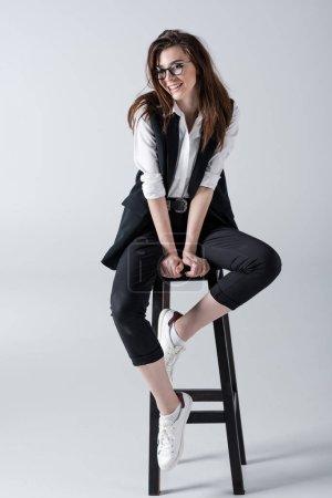 Photo pour Belle jeune femme hipster élégant assis sur le tabouret et souriant à la caméra - image libre de droit