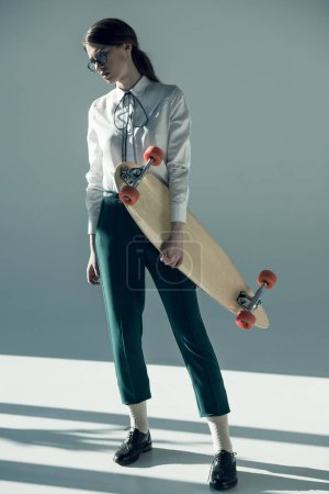 hipster woman holding skateboard