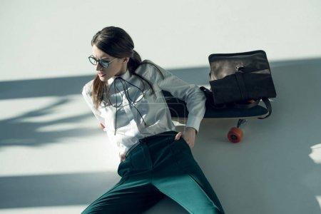 Photo pour Jeune femme hipster élégant dans des lunettes et chemise blanche couché sur le sol avec planche à roulettes, sac à dos et regarder loin - image libre de droit