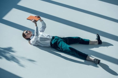 Photo pour Side view of young stylish hipster woman in glasses holding digital tablet while lying on floor - image libre de droit