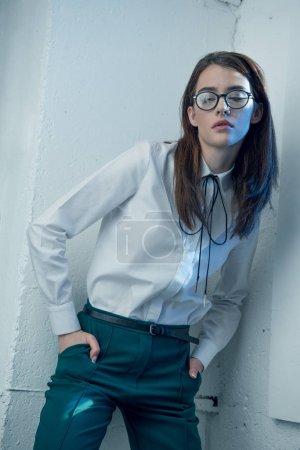 Photo pour Jeune femme hipster élégant dans des lunettes et chemise blanche avec les mains dans les poches détournant les yeux - image libre de droit