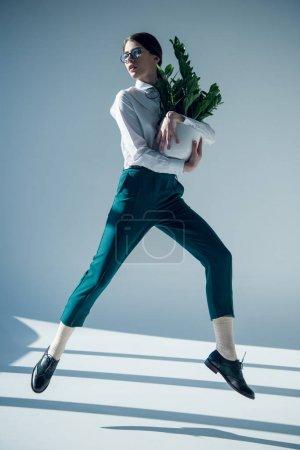 Photo pour Jeune femme hipster élégant en chemise blanche et lunettes sautant avec la plante verte dans le pot de fleurs dans les mains - image libre de droit