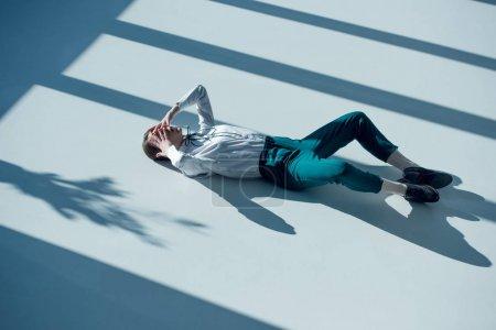 Photo pour Jeune femme hipster élégant en chemise blanche et pantalon vert couché sur le sol avec les mains sur les yeux - image libre de droit