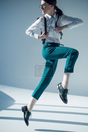Photo pour Jumping angry stylish hipster woman in white shirt, green trousers and glasses - image libre de droit