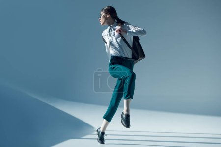 Photo for Young stylish hipster woman in white shirt, green trousers and glasses looking away while jumping - Royalty Free Image