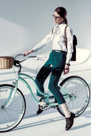 Photo pour Young stylish hipster woman in glasses, white shirt and green trousers with hipster bicycle - image libre de droit