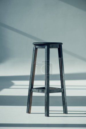 Photo for View of wooden bar stool with shadows on grey - Royalty Free Image
