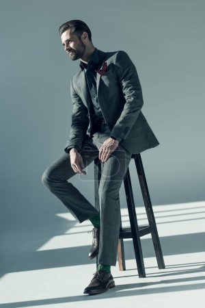 Photo for Handsome stylish man in elegant suit sitting on stool and looking away - Royalty Free Image