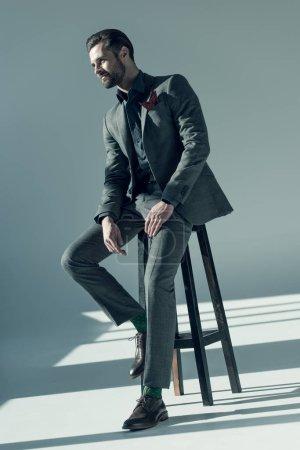 Photo pour Charmant homme élégant en costume élégant assis sur un tabouret et regardant ailleurs - image libre de droit