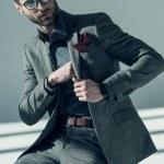 Handsome stylish man in eyeglasses sitting on stoo...