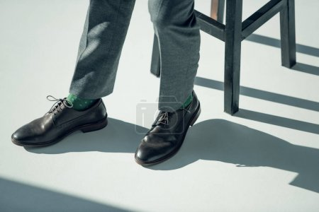 Photo for Close-up partial view of man in stylish shoes and elegant trousers sitting on stool - Royalty Free Image