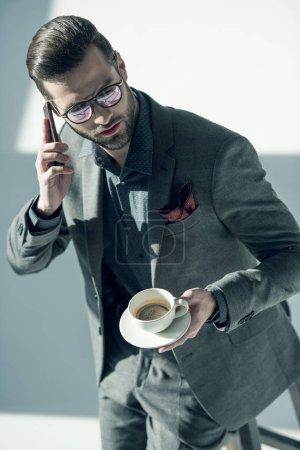 Photo pour Charmant homme d'affaires élégant avec des lunettes tenant une tasse de café et parlant sur smartphone - image libre de droit