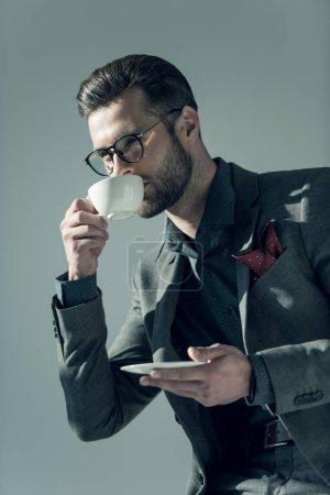 Photo for Elegant bearded man in eyeglasses drinking coffee on grey - Royalty Free Image