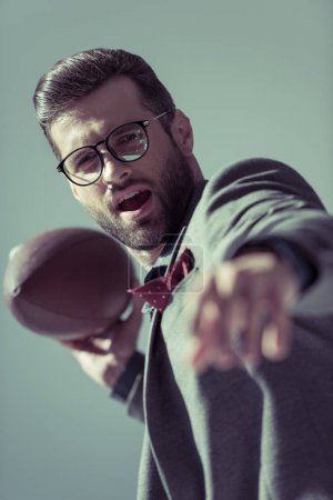 Photo for Excited stylish man in eyeglasses throwing rugby ball on grey - Royalty Free Image
