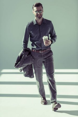 Photo for Fashionable smiling man in eyeglasses walking with paper cup and jacket in hand - Royalty Free Image