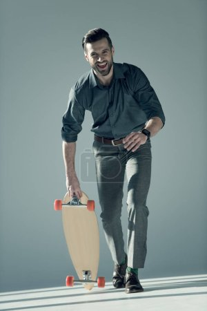 Photo for Cheerful stylish man holding skateboard on grey - Royalty Free Image