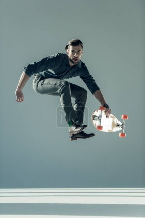 Fashionable man holding skateboard