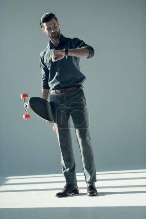 Photo pour Homme élégant tenant skateboard et regardant regarder sur gris - image libre de droit